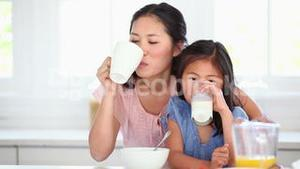 Mother and daughter drinking as they sit together