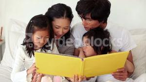 Family reading a book as they sit together