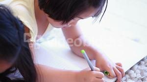 Girl colouring while lying next to her sister