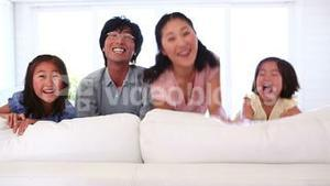 Family jumping out from behind a sofa