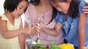 Daughters helping their father toss salad