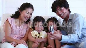 Family taking a picture of themselves as they sit together