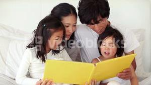 Parents reading a book to their children