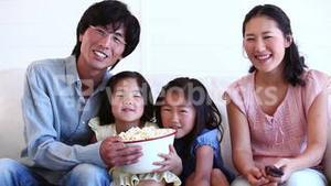 Family watching television while eating popcorn