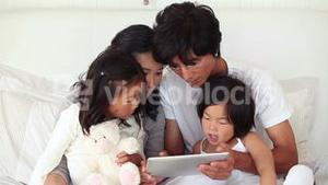 Family concentrating on a tablet computer