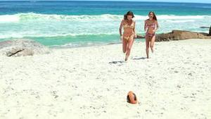A pair of women in bikinis running towards a rugby ball