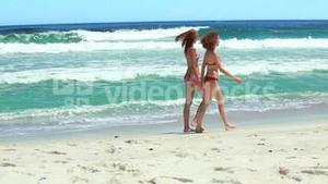 Two friends walking along the beach together