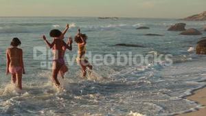 Four women at the beach playing in the water