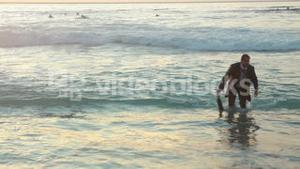 Business man walks out of the ocean