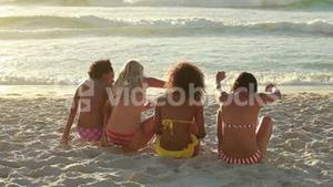 Four girls sitting on the beach together