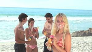 Four attractive people standing with cocktails at the beach