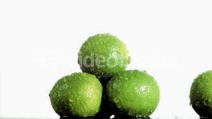 Three delicious limes in super slow motion being soaked