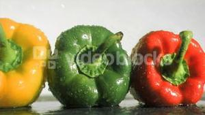 Colorful peppers in super slow motion receiving water