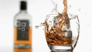Ice cubes in super slow motion falling in a glass of whiskey