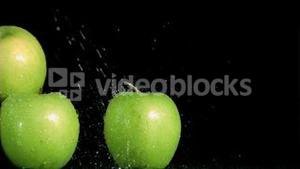 Green apples watering in super slow motion