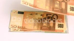 Wind blowing in super slow motion on euro banknotes