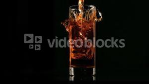 Ice cube falling in super slow motion in apple juice