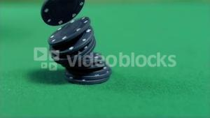 Black gambling chips falling in super slow motion