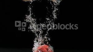 Red apple diving in super slow motion into water
