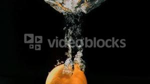 Orange falling in super slow motion into water