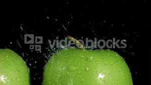 Green apples watered in super slow motion