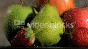 Rain falling in super slow motion on fruits