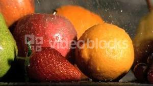 Rain falling in super slow motion on many fruits