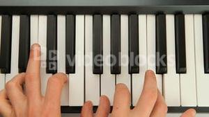 Fingers typing on piano keys