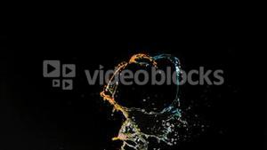 Colorful trickles of water in super slow motion mixing