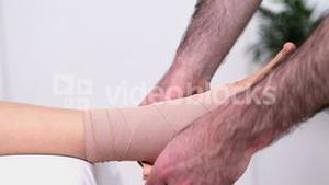 Physiotherapist strapping the ankle of his patient