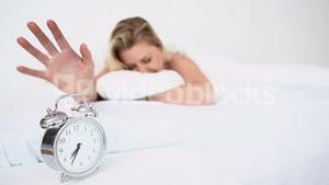 Alarm clock ringing while a woman sleeps