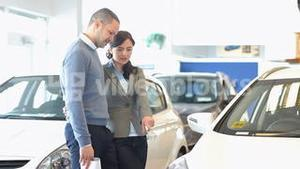 Stylish couple looking at a car