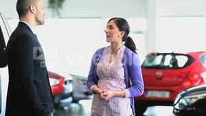 Businessman giving car keys while shaking hands