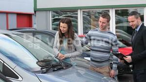 Businessman presenting a car to a couple