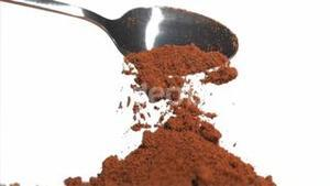 Slow motion of brown powder being poured
