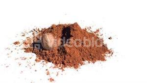 Nutmeg falling in super slow motion into brown powder