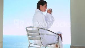 Woman drinking a coffee with a sea view