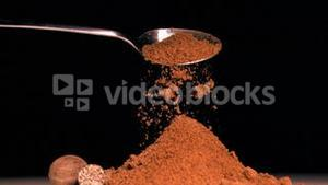 Spoon pouring powder in super slow motion on piled up powder