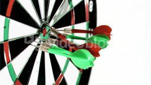 Darts grouped together in super slow motion being thrown on a dart board