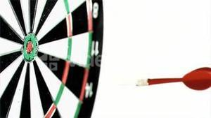 Plastic red dart in super slow motion being thrown on a dart board