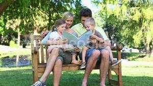 Family sitting on a bench reading a book