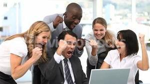 Happy business team looking at a computer