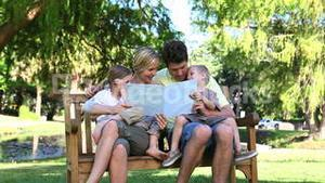 Family reading a book while sitting on a bench