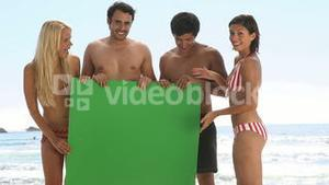 Friends holding a green board on the beach