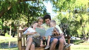 Family looking at a book in a park