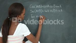 Video of a black student writing on a blackboard
