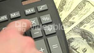 Hand typing on a calculator surrounded by bills
