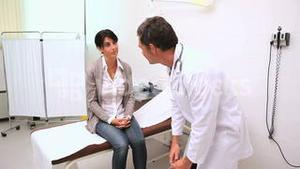 Doctor testing knees reflex of a patient