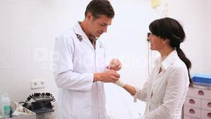 Doctor doing a bandage at patient wrist