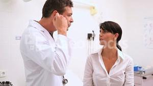 Concentrated doctor auscultating a patient with a stethoscope